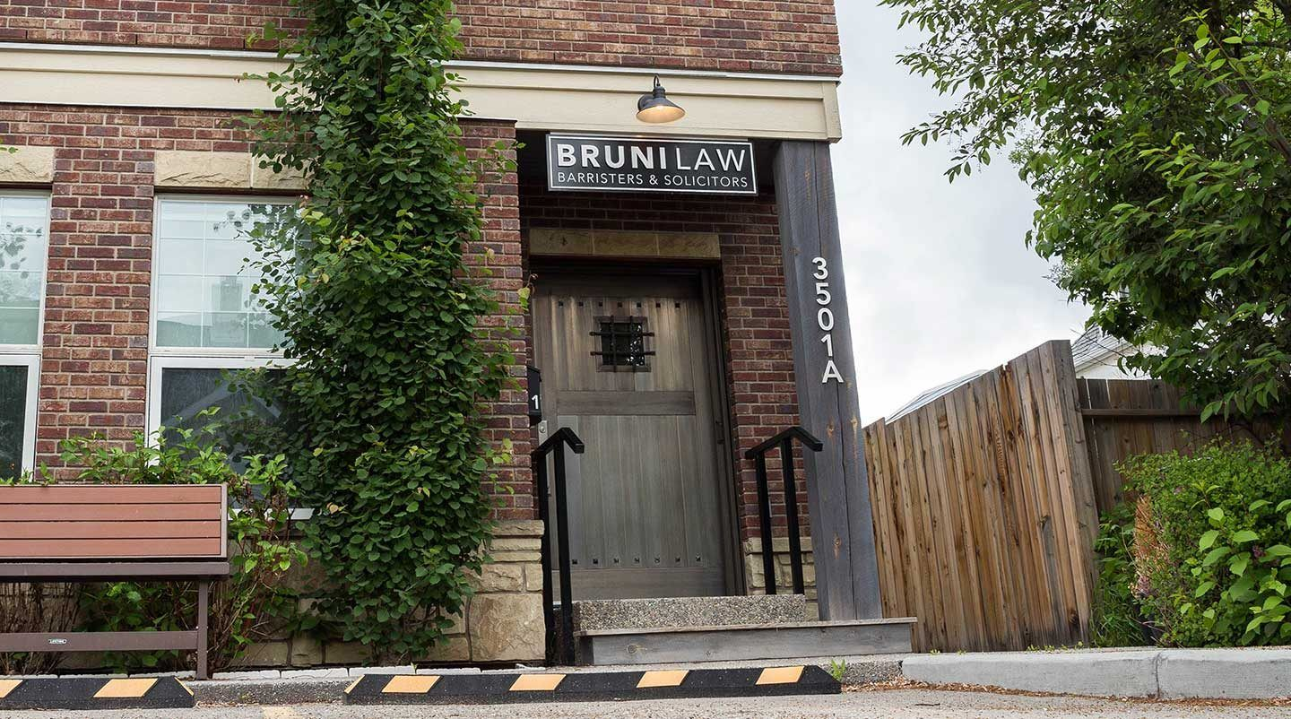 exterior of a heritage brick building with ivy growing up the side and a Bruni law sign above the door