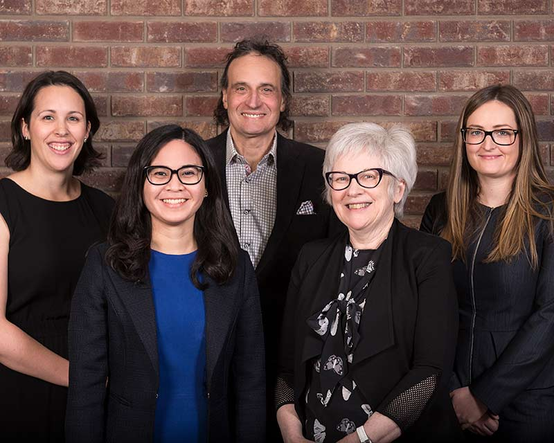 group photo of three young women older man and older woman against brick wall